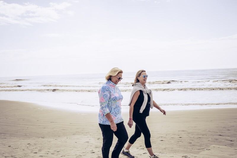 Two woman walking on the beach as part of their exercise routine for better sleep hygiene