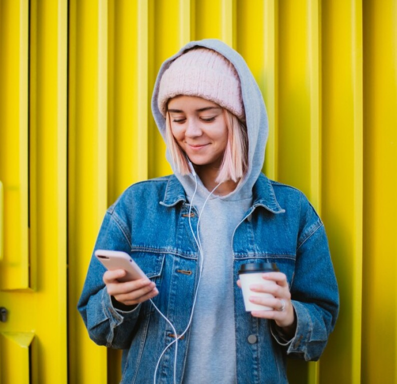 Woman with pink hair standing outside using her phone and drinking coffee