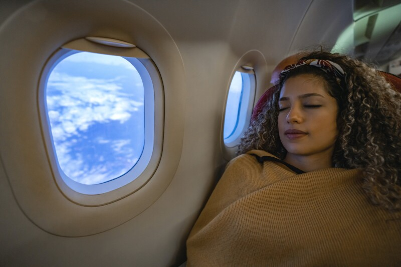 Woman on a plane, sleeping with the window open