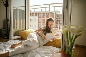 Woman lying on bed next to balcony reading a book.