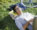 College student sleeping in quad with books as a pillow