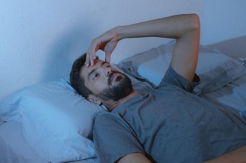 Man struggling with sleep anxiety, wide awake at night