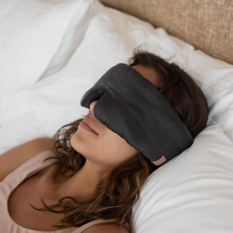 Woman in bed wearing a Lunya Sleep Mask