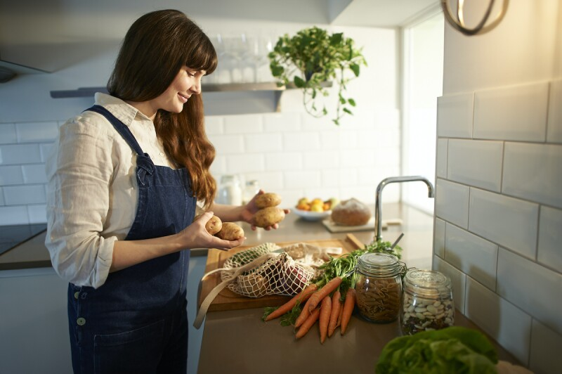 Woman unpacking fresh vegetables in a kitchen for a plant-based diet to treat acid reflux at night