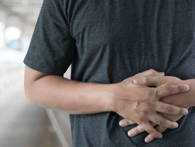 Man clutching his stomach from acid reflux pain