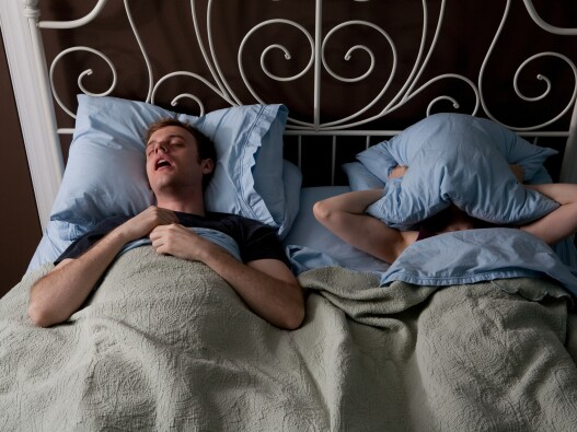 Person covering their face with a pillow next to their snoring bed partner