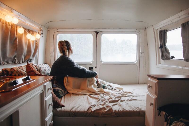 Woman sitting up in bed on a camper van mattress