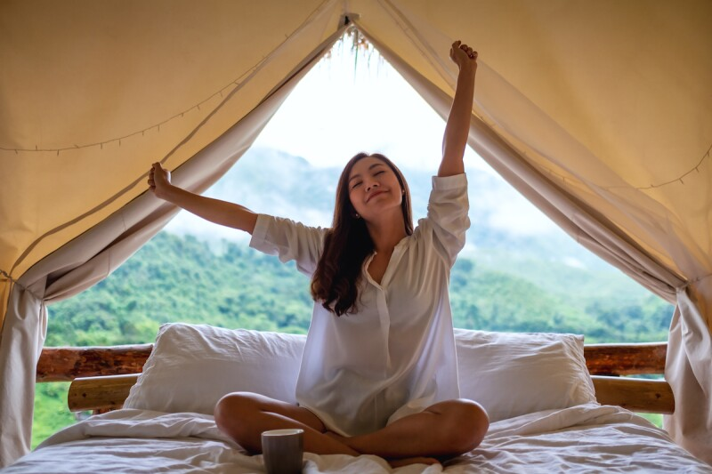 a young woman do stretching after waking up in the morning with a beautiful nature view outside the tent