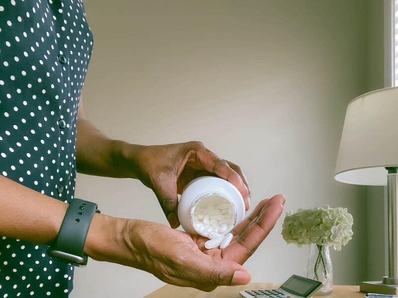 Woman pouring supplements from a bottle for menopause symptoms
