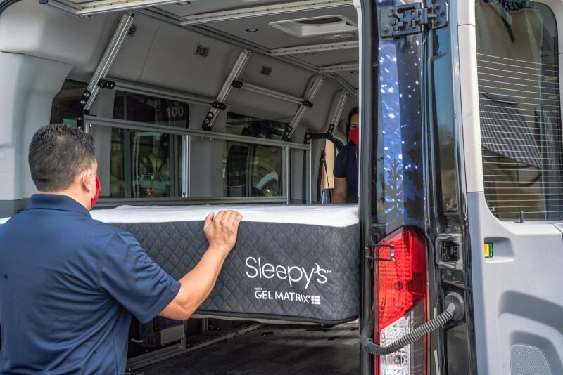 Mattress Firm Sleep Experts load a Sleepy's mattress into a camper van.