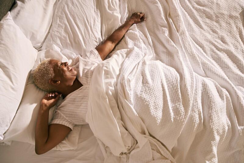 Older Black woman waking up happy
