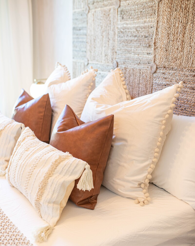 A variety of guest bedroom pillows on a bed.