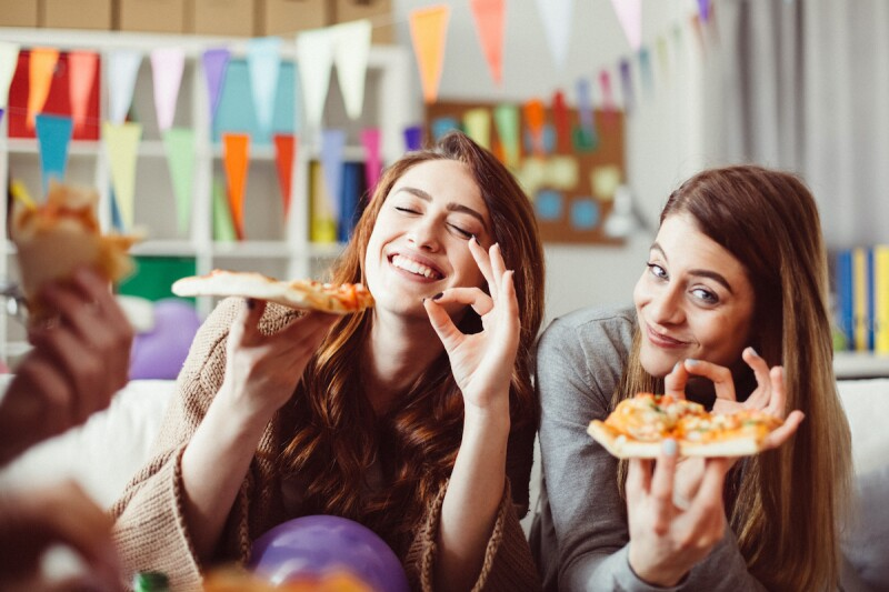 Two adults eating delicious pizza at a slumber party