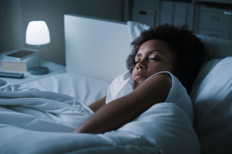 Person laying in bed, getting ready to winddown and sleep for 7 to 8 hours