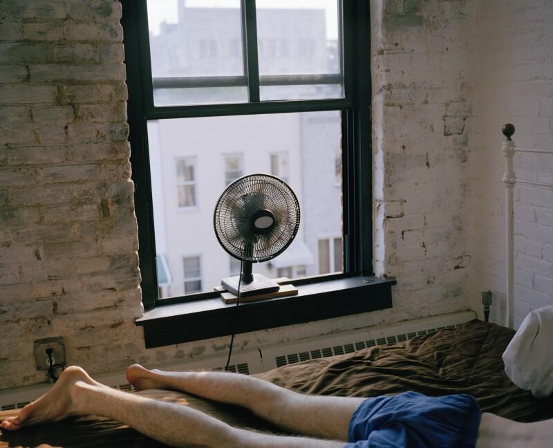 Legs on a mattress in a hot room with a window fan