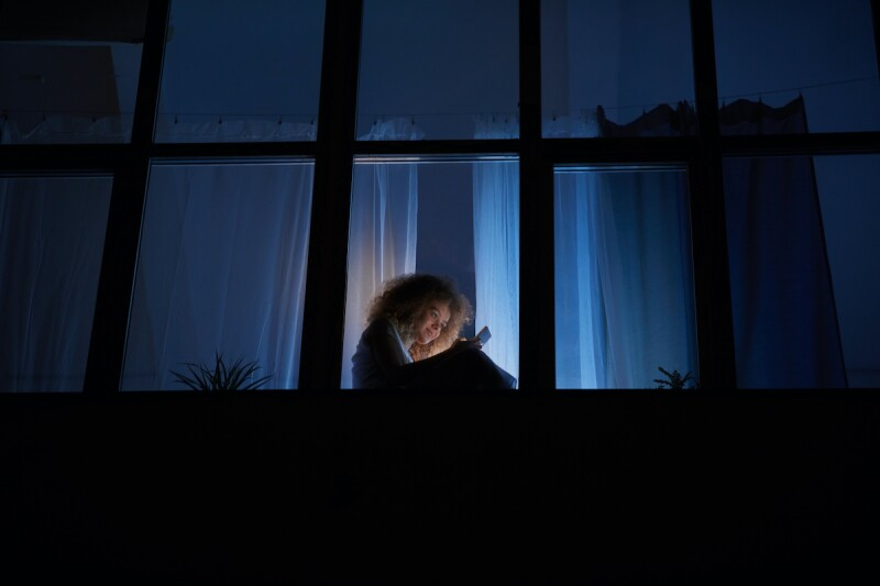 Girl texting on her phone in the middle of the night, wide awake