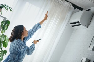 Woman adjusting air conditioner unit to create a better sleep environment for her room
