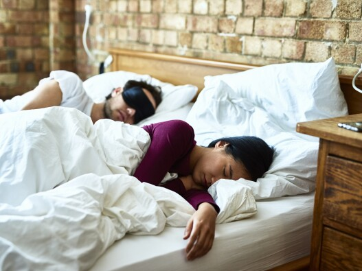Couple sleeping in a bed together in daylight