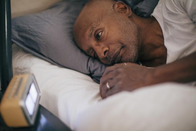 Retired senior man lying in bed looking at alarm clock