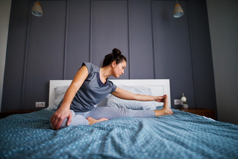 Woman doing bedtime yoga in bed