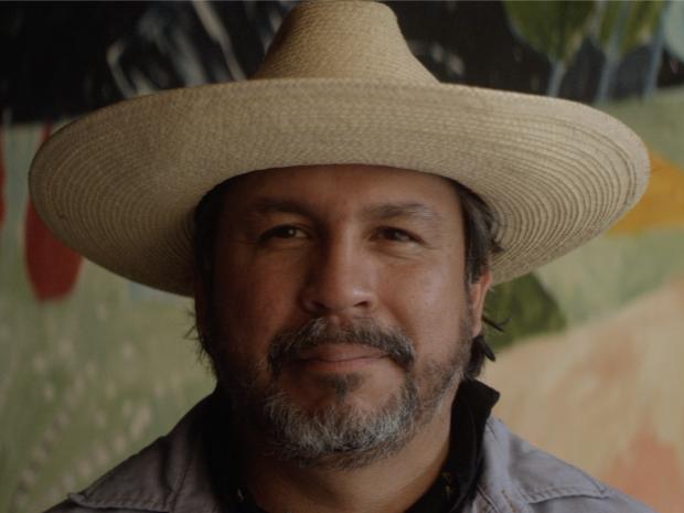 Texas artist Cruz Ortiz standing in front of one of his paintings.