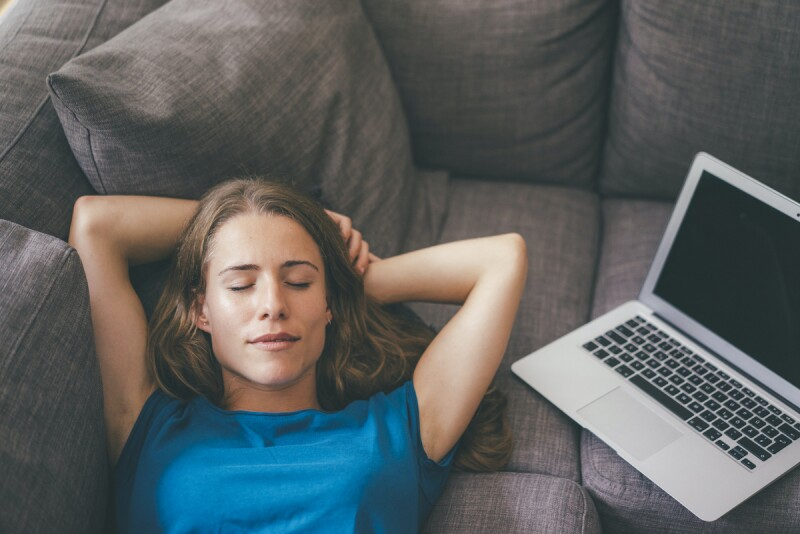 Person lying down with their eyes closed to take a break from work