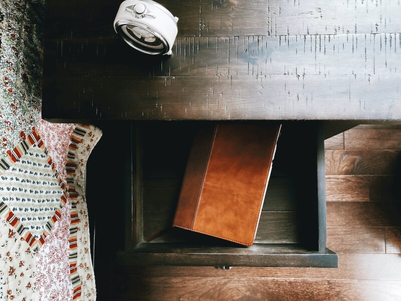 A wooden nightstand with a journal inside the drawer