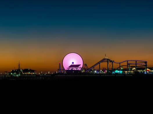 Long exposure shot of a pink ferris wheel at night, in an amusement park
