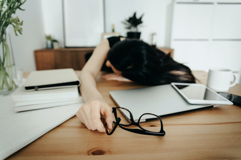 Sleep deprived person laying on desk, falling asleep out of exhaustion