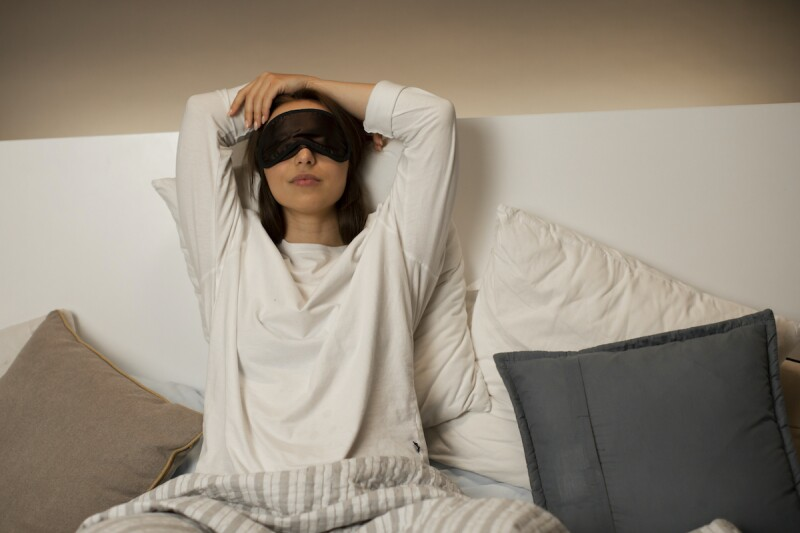 Woman wearing an eye mask and engaging in a relaxation routine to prevent restless sleep
