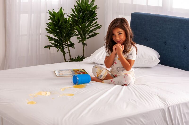 Child spilling juice on a mattress protector.jpg