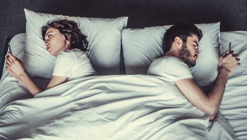A man and a woman use their cellphones in bed with their backs to each other.