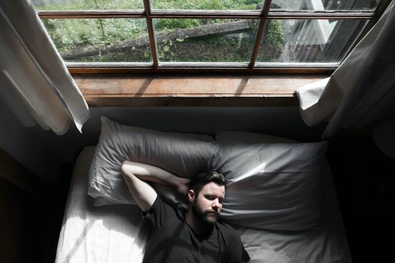 Man falling asleep in bed