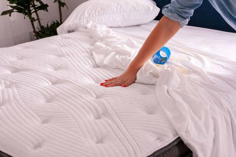 A hand with red fingernails checking out a mattress protector.