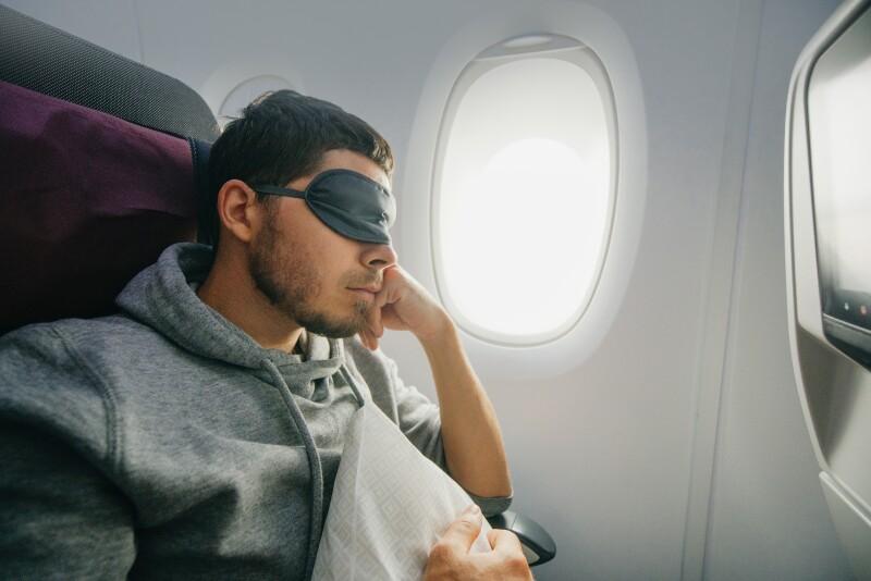 Travel Sleep: Man wearing an eyemask on a plane