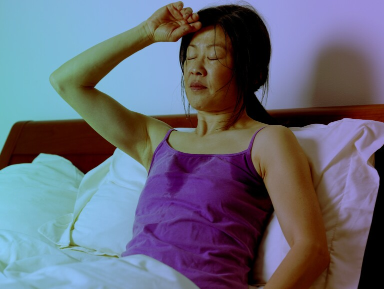 Woman experiencing hot flashes and night sweats.