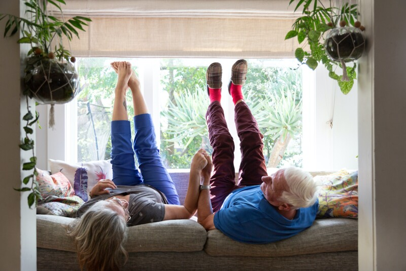 Two older adults with a strong relationship holding hands while lying on the couch