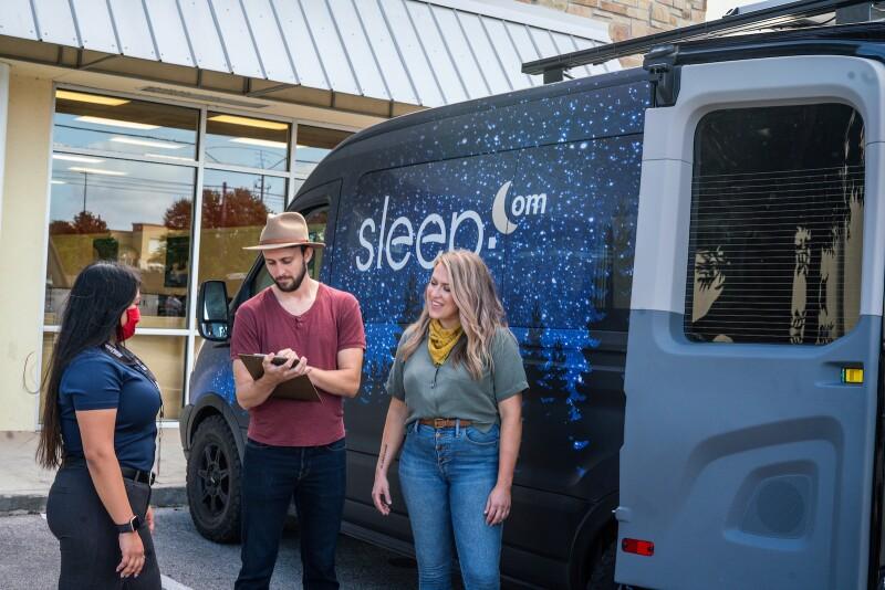Camper van travellers talk to Mattress Firm Sleep Expert outside of a Mattress Firm store.
