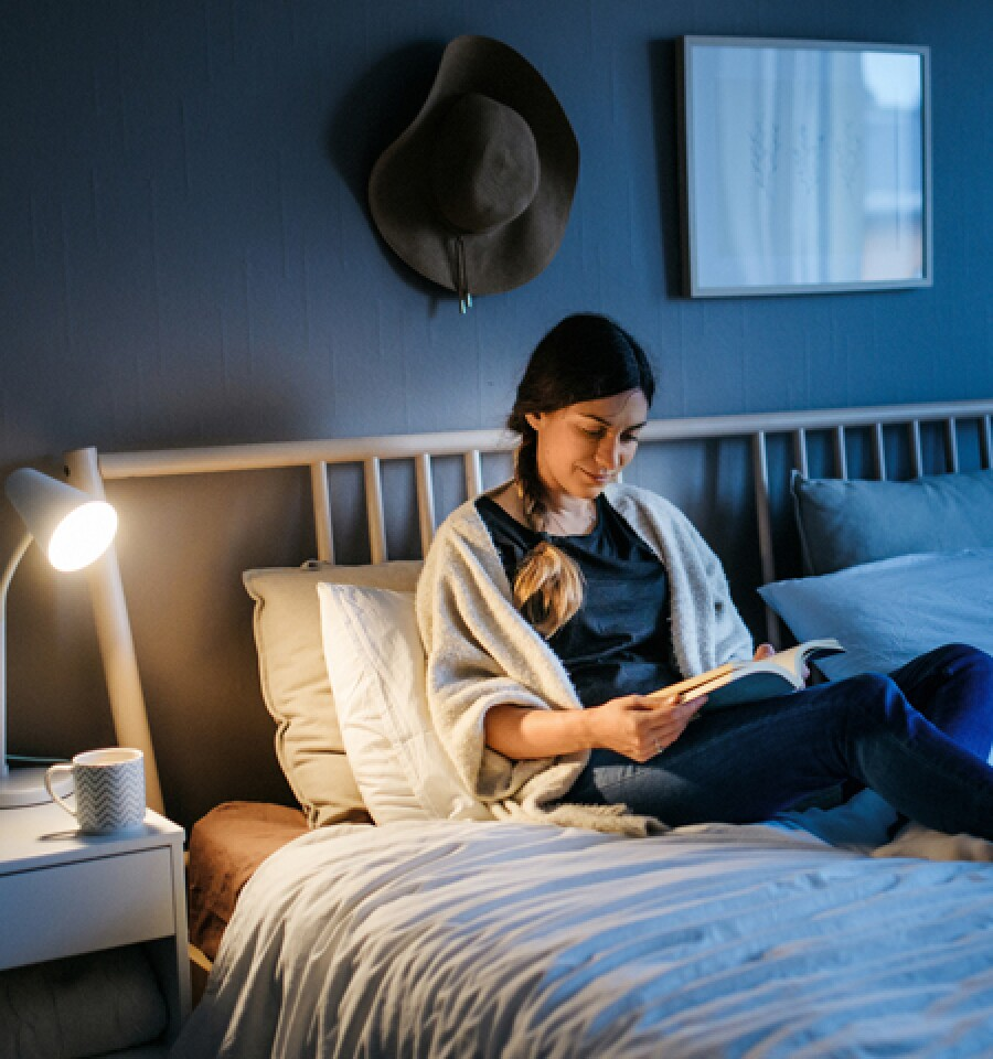 Woman reading paperback book at night with a bedside lamp