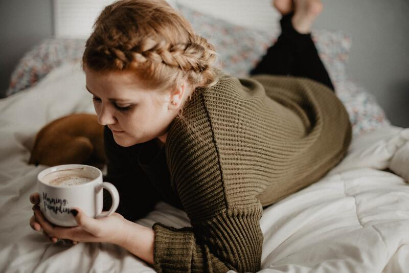 Woman drinking coffee out of a mug in bed.
