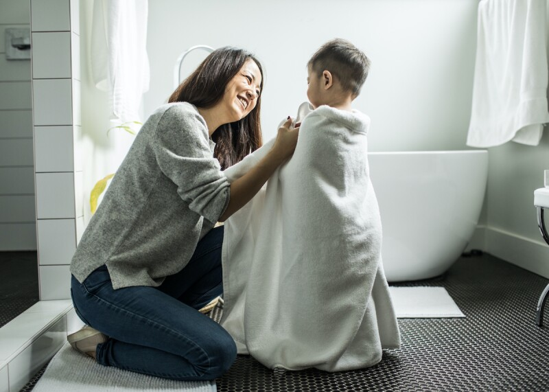 Parent drying young child from a bath before bedtime