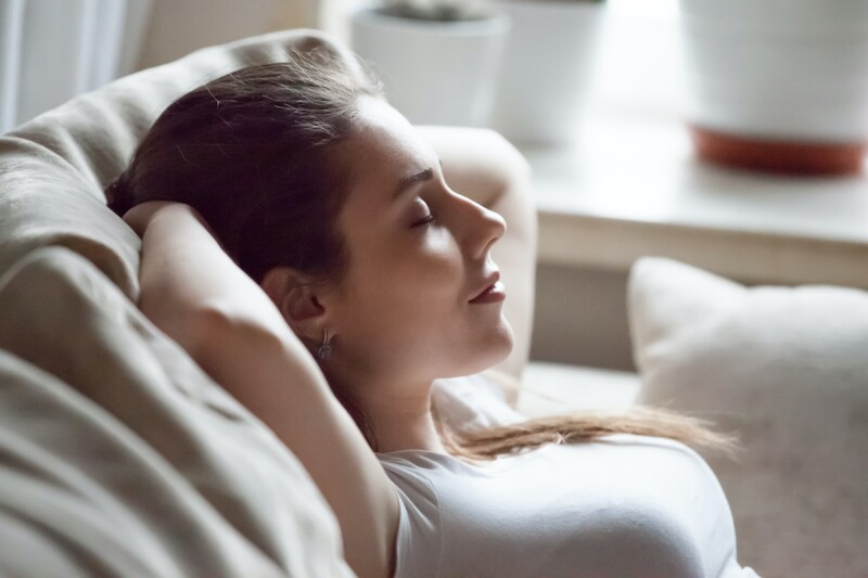 Close up of person in bed, meditating before bed to manage sleep anxiety