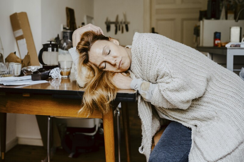Woman laying her head on her desk with coffee cups in the background