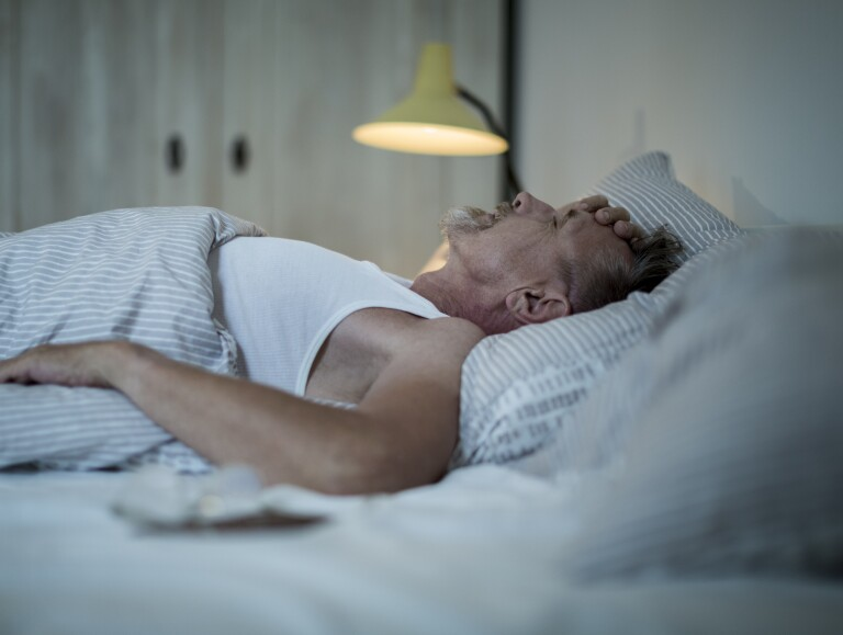 Senior man in his early 60s with a greying beard is sleepless in bed because of an uncomfortable mattress.
