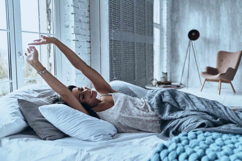 Woman stretching and waking up after having a good night of sleep in a cozy bedroom