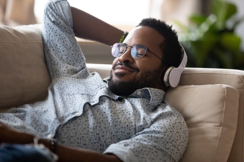 Serene african man lying on sofa wear headphones listen music