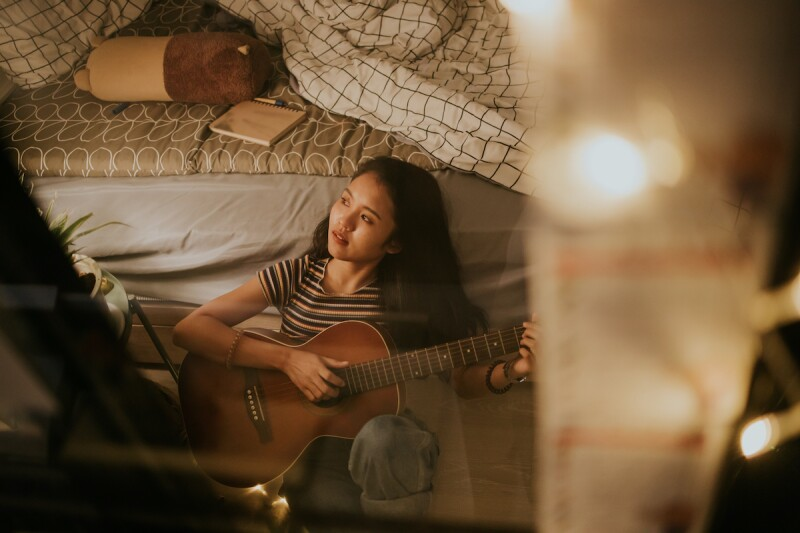 Person with night owl chronotype playing a guitar to relax and meditate at night before bedtime