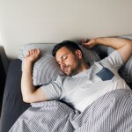 Man sleeping on his back in bed with pinstripe sheets