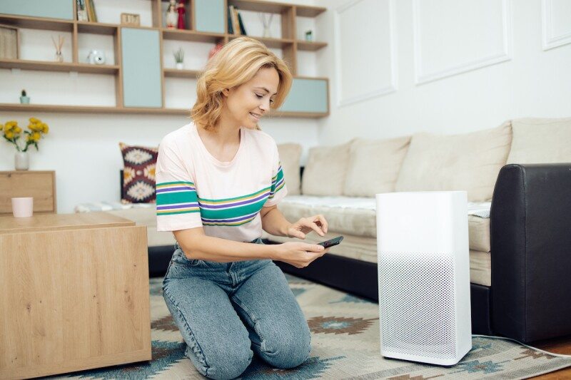 Woman using an air purifier for her allergies at night