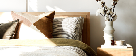 Fully made bed with patterned pillows next to a wooden nighstand with a vase, bowl, book, and essential oil